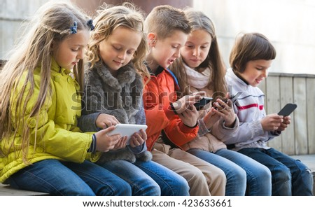 Happy kids sitting on bench with mobile devices in street