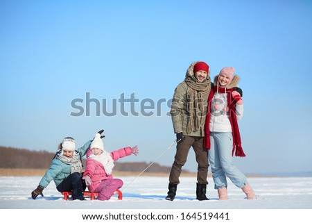 Happy kids sitting on sledge while their parents near by