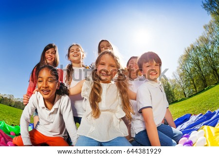 Happy kids sitting together on lawn at sunny day
