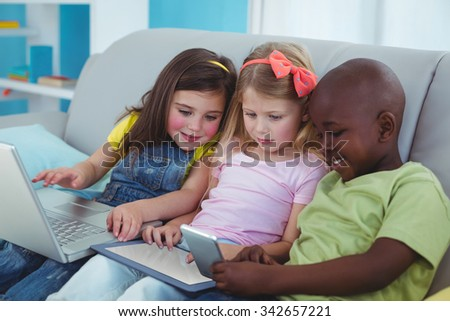Happy kids sitting together with a tablet and laptop and phone on the couch - stock photo