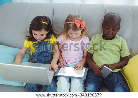Happy kids sitting together with a tablet on the couch - stock photo