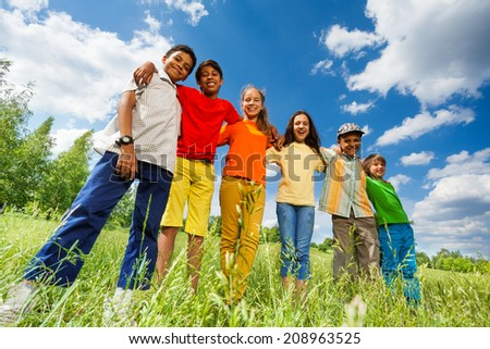 Happy kids stand in row straight and hug - stock photo