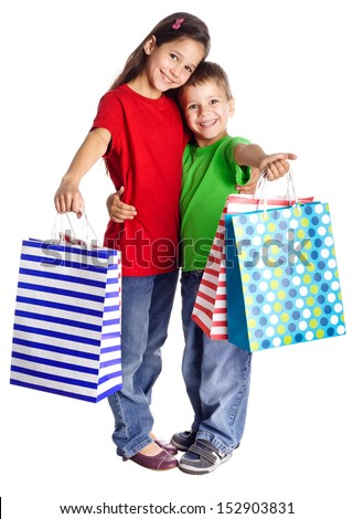Happy kids standing with shopping bags, isolated on white - stock photo