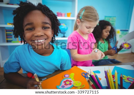 Happy kids using modelling clay together at their desk - stock photo