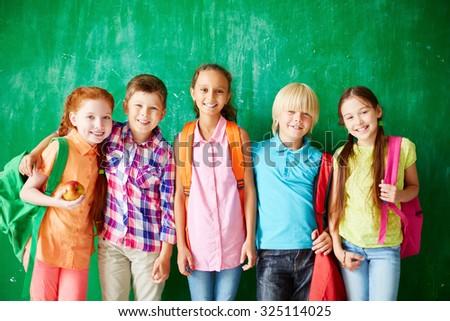 Happy kids with backpacks standing in row along school blackboard - stock photo