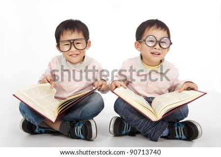 Happy kids with big book wearing black glasses - stock photo