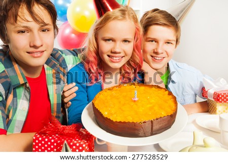 Happy kids with birthday cake and candle - stock photo