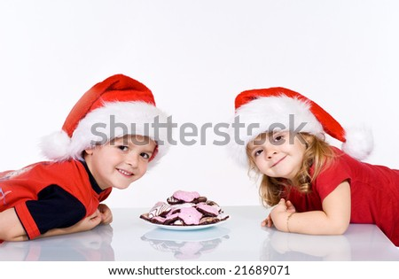 Happy kids with christmas cookies and santa hats  on white background