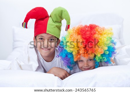 Happy kids with clown hat and hair playing indoors - stock photo