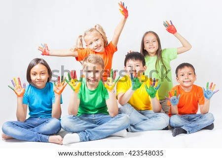 Happy kids with painted hands smiling and posing at white background. Funny children. International Children's Day. Indian, asian, caucasian - multiracial ethnicity - stock photo