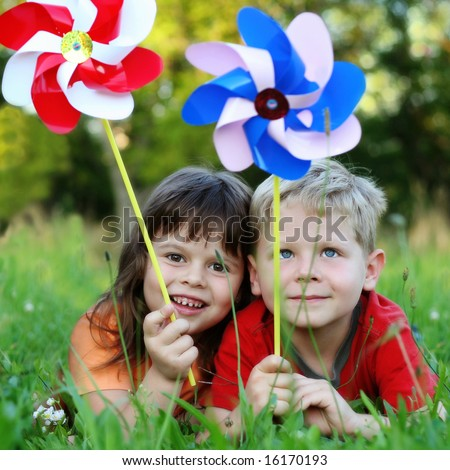 Happy kids with pinwheels on grass - stock photo