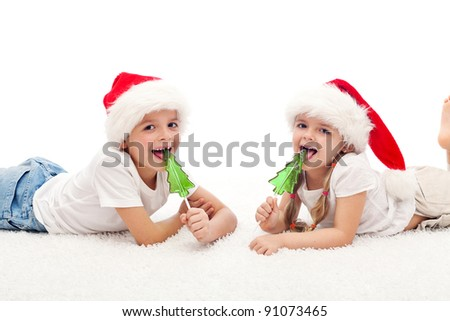 Happy kids with santa hats and fir tree shaped candy