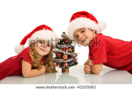 Happy kids with santa hats and small christmas tree - isolated - stock photo