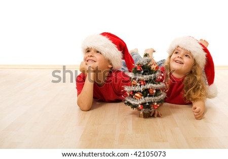 Happy kids with santa hats laying on the floor - isolated with copy space - stock photo