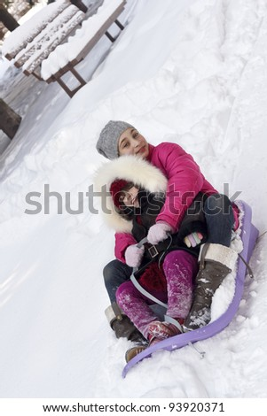 Happy kids with skate sled in winter time - stock photo