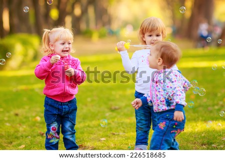 Happy kids with soap bubbles in the park.  children's emotions - stock photo