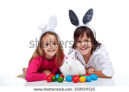 Happy kids with the easter bunny and colorful eggs - wearing bunny ears - stock photo