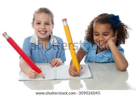 Happy kids writing down their homework  - stock photo