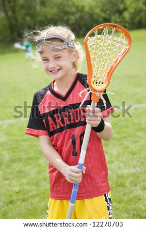 Happy lacrosse player with her stick - stock photo