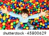 Happy lad seated on colorful balls and stretching arms to camera - stock photo