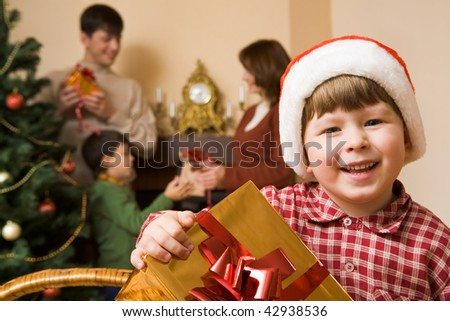 Happy lad with gift in hands looking at camera with smile on Christmas day - stock photo