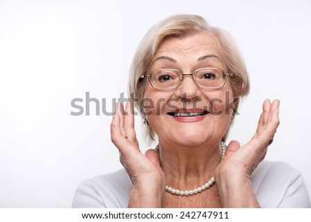 Happy lady. Beautiful senior woman smiling at camera and raising hands while standing against white background - stock photo
