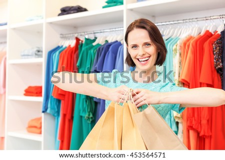 Happy lady boasting of purchase in shop - stock photo