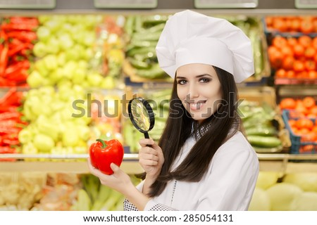 Happy Lady Chef Inspecting Vegetables with Magnifying Glass - Portrait of a young female cook in a grocery store checking for best quality ingredients   - stock photo
