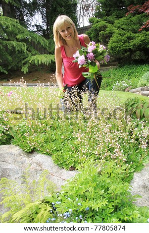 Happy lady in the garden with cut flowers. - stock photo
