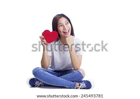 Happy lady sitting on the floor in casual outfit holding a heart shaped red card.