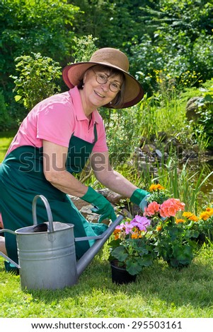 Happy lady transplanting spring flowers from the nursery into her garden kneeling on the green lawn with a watering can smiling at the camera