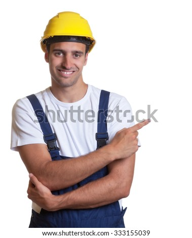 Happy latin construction worker pointing sideways