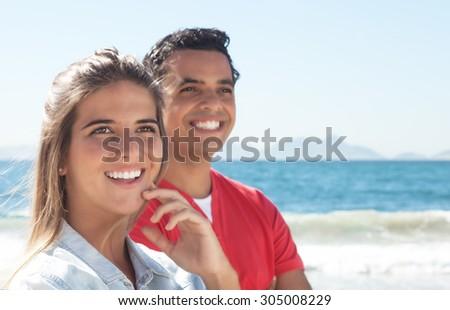 Happy latin couple at beach - stock photo
