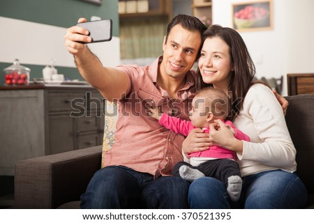 Happy Latin couple taking a selfie of themselves with their baby girl using a smartphone at home - stock photo