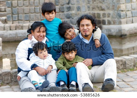 Happy Latin family sitting in the street - stock photo