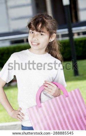 Happy latin girl smiling with shopping bags outdoors