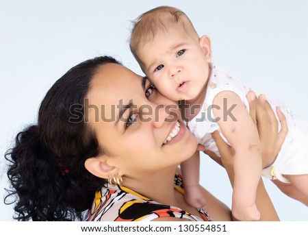 Happy latin mother carrying her baby girl - stock photo