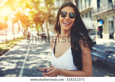 Happy Latin woman in summer sun glasses smiling brightly while holding smart phone strolling outdoors in the city at sunny day,female person using mobile standing with composition copy space on a side - stock photo