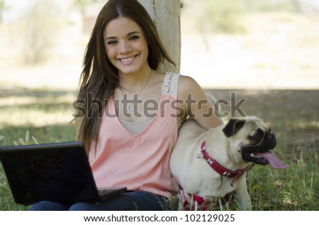 Happy latin woman spending time with her dog at the park - stock photo