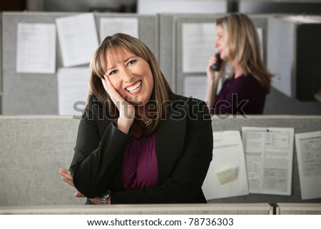 Happy Latina office worker rests a hand on her face