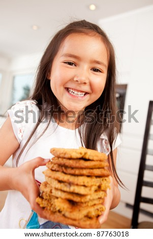 Happy, laughing and smiling young cute girl holding stack of large home made cookies