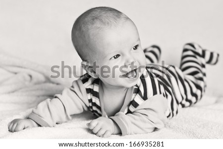 happy laughing baby boy lying on his stomach  (black and white) - stock photo