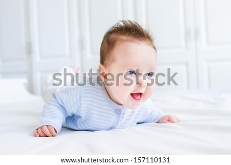 Happy laughing baby enjoying her tummy time in a white nursery - stock photo