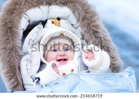 Happy laughing baby girl enjoying a walk in a snowy winter park sitting in a warm stroller with sheepskin hood wearing a white jacket and hat - stock photo