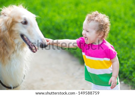 Happy laughing baby playing with a big dog - stock photo