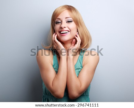 Happy laughing blond young woman holding hand at face on blue background with empty copy space - stock photo