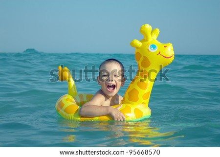 happy laughing boy enjoying swimming in sea with rubber ring giraffe - stock photo