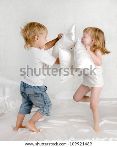happy laughing brother and sister  having a pillow fight in bed at home - stock photo