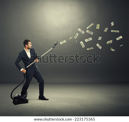 happy laughing businessman holding vacuum and catching paper money over dark background - stock photo