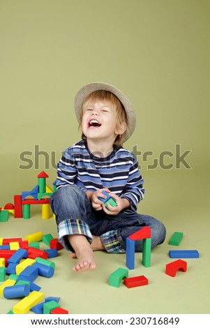 Happy, laughing, Child, kid, playing with building blocks. Fashion and clothing concept.